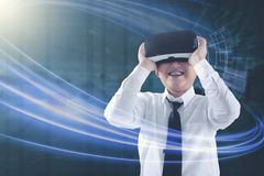 Amazed kid looking at his virtual reality headset. With futuristic background Stock Image