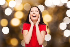 Amazed laughing woman in red dress looking up. Happiness and people concept - amazed laughing young woman in red dress looking up over lights background Stock Photos