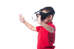 Amazed little asian boy looking in a VR goggles and gesturing wi stock image