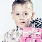 Amazed little boy with gift boxes. Happy childhood, holidays christmas time. Little happy boy amazed child with pink presents gift boxes. Positive emotion Royalty Free Stock Images