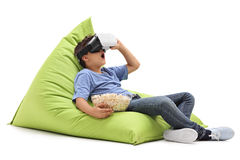 Amazed little boy looking in VR goggles. And eating popcorn seated on a beanbag isolated on white background Royalty Free Stock Photography