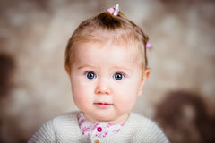 Amazed little girl with big grey eyes and plump cheeks. Close-up studio portrait on brown grunge background royalty free stock photos