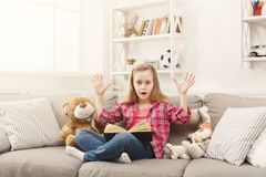 Amazed little girl with book and her favorite toys at home. Surprised little girl at home with book among her favorite toys. Kid with hands up reading exiting Royalty Free Stock Image