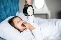 Amazed little girl holding alarm clock, covering her mouth while lying in soft bed. Amazed little girl holding clock, covering her mouth while lying in soft bed Stock Image
