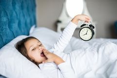 Amazed little girl holding alarm clock, covering her mouth while lying in soft bed. Amazed little girl holding clock, covering her mouth while lying in soft bed Stock Photos