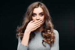 Amazed lovely woman covering mouth with hand