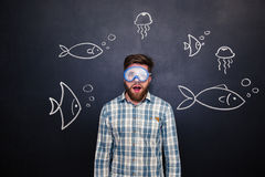 Amazed man in diving mask with open mouth over blackboard Stock Image