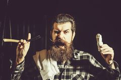 Bearded man shaves with razor. Amazed man, handsome, bearded hipster, brunette with long beard and moustache shaves with vintage razor with open blade and stock photos