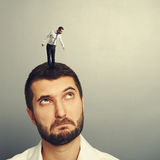 Amazed man looking up at small man. On the head Royalty Free Stock Photo