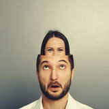 Amazed man looking up at woman in his head. Amazed young men looking up at hiding smiley women in his head. photo over grey background Royalty Free Stock Image