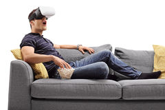 Amazed man looking in VR goggles. Amazed young man looking in VR goggles and eating popcorn seated on a sofa isolated on white background Royalty Free Stock Photo