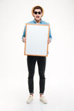 Amazed man with mouth opened shouting and holding blank whiteboard Royalty Free Stock Image