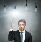 Amazed man with open mouth and light bulbs overhead Stock Photos