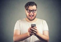 Amazed man with phone reading news stock photography