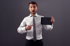 Man pointing at his tablet pc. Amazed man pointing at his tablet pc and looking at camera Royalty Free Stock Images