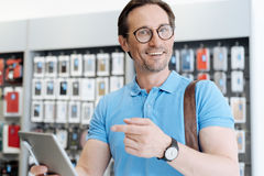 Amazed man pointing toward tablet and smiling into camera. Have you seen thi one. Excited male customer wearing glasses standing at a display and trying out a Stock Photos