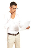 Amazed man reading a paper. Amazed business man reading a paper isolated on white background Royalty Free Stock Image