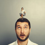 Amazed man with small angry woman. Amazed men with small angry women on the head over grey background Royalty Free Stock Photo