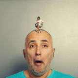 Amazed man with small angry woman. Amazed men with small angry women on his head over grey background Royalty Free Stock Photo