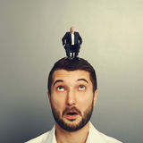 Amazed man with small happy man. Amazed men with small happy men on the head Royalty Free Stock Photography