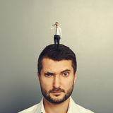 Amazed man with small unhappy man. On the head Royalty Free Stock Photo