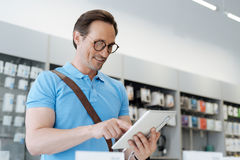 Amazed man smiling while testing mockup digital tablet. This one is real dream. Male shopper looking for a new gadget and trying out all the technological Royalty Free Stock Images
