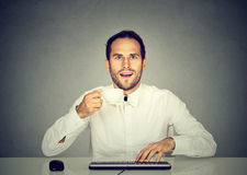 Amazed man using computer holding cup of coffee Royalty Free Stock Photography