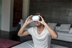 Amazed man with virtual reality headset. Sitting at home Royalty Free Stock Image