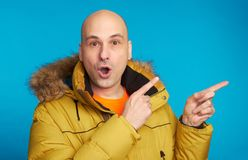 Amazed man wearing coat pointing with forefinger. Amazed bald man wearing winter coat, looking with widely opened mouth at camera, pointing with forefinger at Royalty Free Stock Images