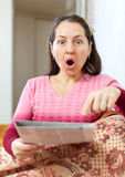 Amazed mature woman looks newspaper Stock Photo