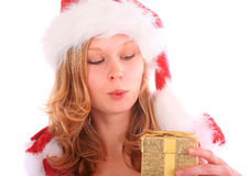 Amazed Miss Santa is holding a golden gift box Stock Image