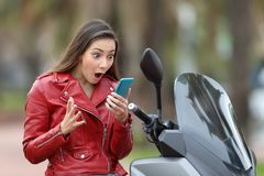 Amazed motorbiker reading exciting news on line. In a smart phone on her motorbike Royalty Free Stock Photography