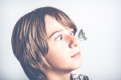Amazed by nature. Child amazed by butterfly over the nose Stock Photography