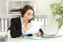 Amazed office worker reading a letter. Amazed office worker reading good news a letter royalty free stock photography