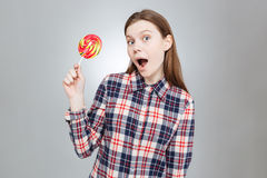 Amazed pretty teenage girl with mouth opened holding lollipop Royalty Free Stock Images