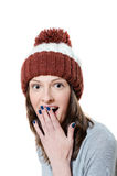 Amazed pretty young girl in winter knitted hat. Isolated closeup picture of amazed pretty young girl in winter knitted hat with her hand over her mouth Stock Images