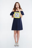 Amazed pretty young woman standing and holding clock Stock Image