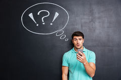 Amazed puzzled young man using cell phone over chalkboard background Royalty Free Stock Photography