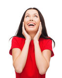 Amazed que ríe a la mujer joven en vestido rojo Imagenes de archivo