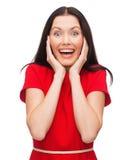 Amazed que ríe a la mujer joven en vestido rojo Imagen de archivo