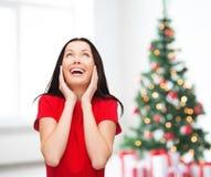Amazed que ríe a la mujer joven en vestido rojo Foto de archivo