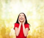 Amazed que ríe a la mujer joven en vestido rojo Foto de archivo libre de regalías