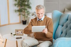 Amazed retired gentleman using his new digital tablet. This is so easy and exciting. Impressed old man relaxing in a chair and smiling cheerfully while working Royalty Free Stock Photos