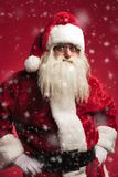 Amazed santa claus standing with hands on waist while snowing. On red background Stock Photo