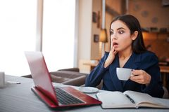 Amazed and scared yougn woman look at laptop screen. She hold one hand on cheek. Another has cup of coffee. Amazed and scared yougn woman look at laptop screen royalty free stock image