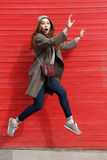 Amazed scared young woman running and jumping. Over red wall background stock photos