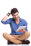 Amazed seated casual man reading good news on  tablet. Amazed young seated casual man reading good news on his tablet pad computer while seated on white Royalty Free Stock Photo