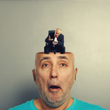 Amazed senior man and angry small businessman. Amazed senior man with open head. angry small businessman screaming with megaphone in the man's head. photo over Royalty Free Stock Image