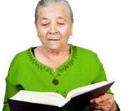 Amazed senior woman reading surprise book Stock Image