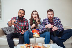 Amazed shocked friends watching tv and eating popcorn on sofa. Group of amazed shocked young friends watching tv and eating popcorn on sofa Royalty Free Stock Photos